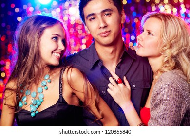 Image of happy girls and guy clubbing together at party