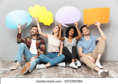 Image of happy group of friends sitting isolated over grey wall background holding speech and thoughtful bubbles.
