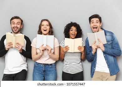 Image of happy group of friends standing isolated over grey wall background looking camera reading books.