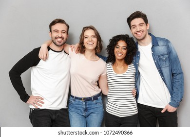 Image of happy group of friends standing isolated over grey wall background looking camera.