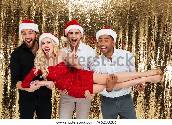 Image of happy group of friends wearing christmas hats standing over glitter bright background with their woman friend on hands. Looking camera.