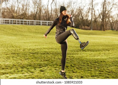 Image of happy handicapped woman 20s in tracksuit doing sports on nature and raising prosthesis leg