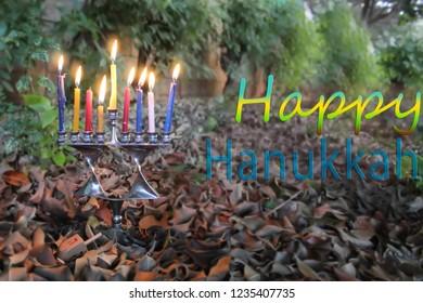 Image for Happy Hanukkah. Hanukkah Menorah in the form of a Jewish star Magen David and Sevivon, Dreidel in Israel. Menorah - candelabrum for Jewish Holiday Hanukkah. Sevivon - Toy of Hanukkah