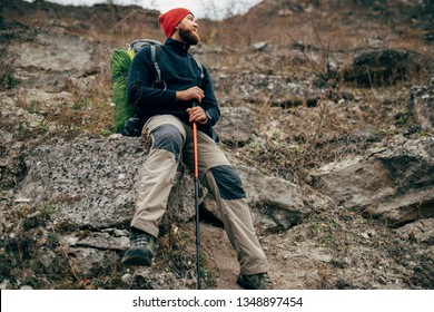 Image of happy hiker young man in green hat, feel good after hiking in mountains. Traveler bearded male smiling and feel happy during trekking in his journey. Travel, lifestyle