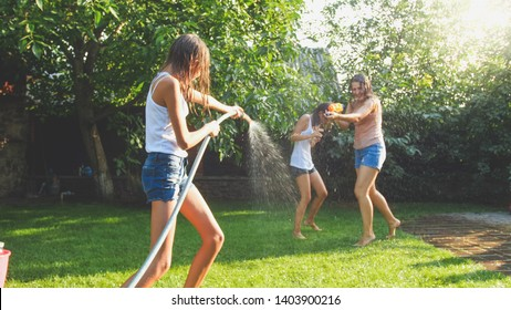 Image of happy laughing family splashing water with water guns and garden hose at backyard. People playing and having fun on hot sunny summer day