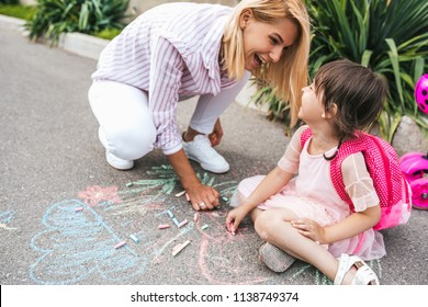 Image of happy little girl and mother laughing and drawing with colorful chalks on the sidewalk. Caucasian female play together with her kid preschooler with backpack outdoor. Mom and child activity
