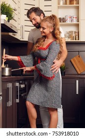 Image of happy loving woman and man preparing food in kitchen at morning