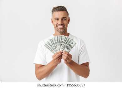 Image of happy man 30s wearing casual t-shirt smiling and holding bunch of money banknotes isolated over white background