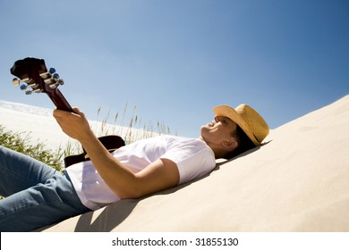 Image of happy man in cowboy hat playing the guitar while relaxing on sandy beach