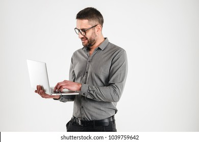 Image of happy man isolated over white background wall looking aside using laptop computer.