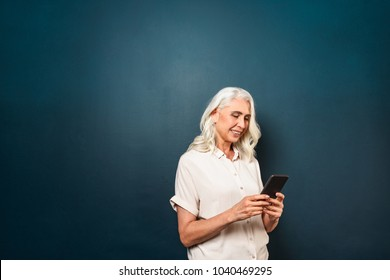 Image of happy mature old woman standing isolated over dark blue background wall looking aside using mobile phone.