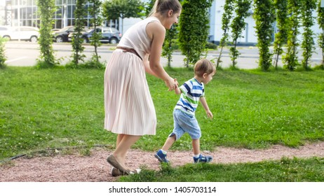Image of happy mother with 3 years old little son playing and running on the children playground at park