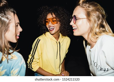 Image of happy multiethnic girls in streetwear smiling and walking at night outdoors