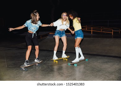 Image of happy multinational girls in streetwear smiling and riding skateboards at night outdoors