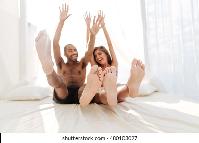 Image of happy multiracial couple laying at the white beach bed with hands up in the air outdoors