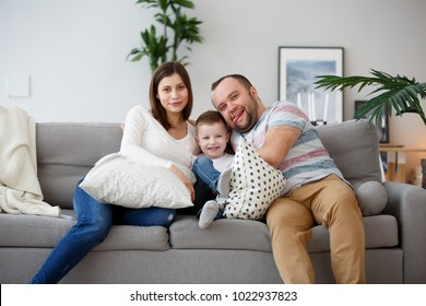 Image of happy parents with son on gray sofa