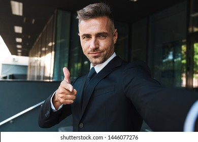 Image of a happy positive mature grey-haired handsome business man outdoors at the street near business center take selfie by camera pointing to you.