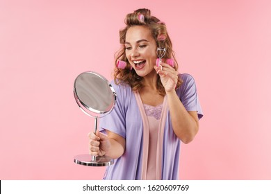Image of happy smiling woman using eyelashes curler and holding mirror isolated over pink background