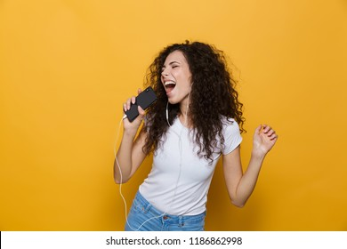 Image of happy woman 20s with curly hair singing while holding smartphone like microphone and listening to music via earphones isolated over yellow background