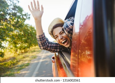 Image of happy woman 20s wearing straw hat laughing and waving hand out of the window while riding in car
