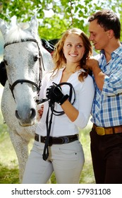 Image of happy woman between purebred horse and her sweetheart outside