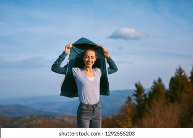 image of a happy woman hiker standing on mountain ridge on the mountains and blue sky background. woman puts on hood sweaters