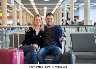 Image of happy woman and man in love looking at camera while sitting in waiting room at airport.