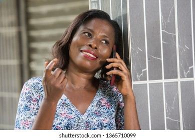 Image of happy woman talking on the phone against the wall outside.