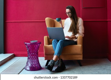 Image of happy woman using laptop while sitting at cafe. Young american woman sitting in a coffee shop and working on laptop
