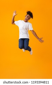 Image of happy young african man jumping isolated over yellow background.
