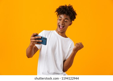 Image of happy young african man posing isolated over yellow background play games by phone make winner gesture.