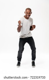 Image of happy young african man standing isolated over white background. Looking camera make winner gesture.