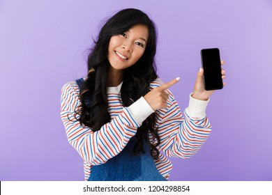 Image of happy young asian beautiful attractive woman posing isolated indoors pointing to display of mobile phone.