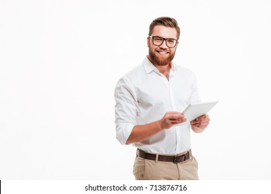 Image of happy young bearded man standing over white wall background isolated. Looking camera using tablet computer.