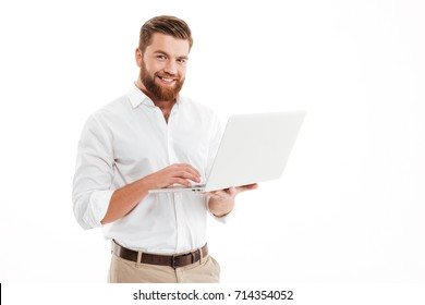 Image of happy young bearded man standing over white wall background isolated. Looking camera using laptop.