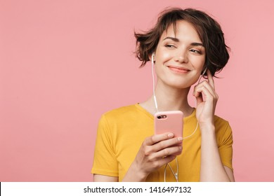 Image of a happy young beautiful woman posing isolated over pink wall background listening music with earphones using mobile phone.