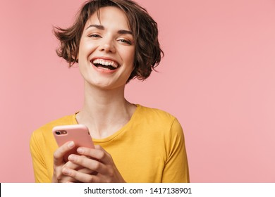 Image of a happy young beautiful woman posing isolated over pink wall background using mobile phone.