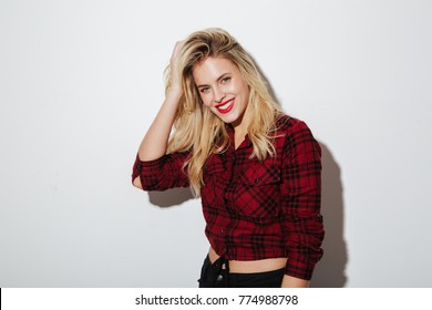 Image of happy young blonde woman standing isolated over white background. Looking camera.