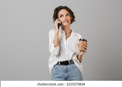 Image of happy young business woman posing isolated over grey wall background talking by mobile phone drinking coffee.