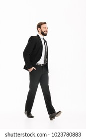 Image of happy young businessman walking isolated over white background. Looking aside.