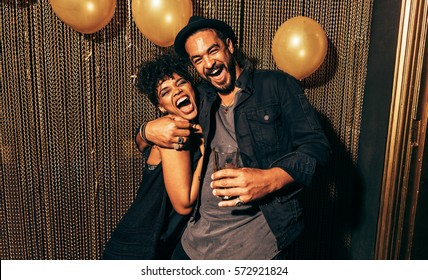 Image of happy young couple having fun at disco. Young man and woman enjoying a party.