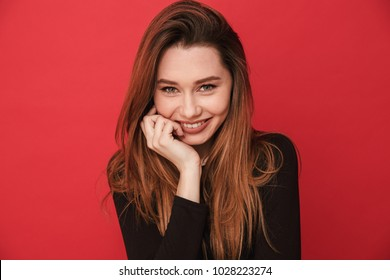 Image of happy young cute woman standing isolated over red background. Looking camera.