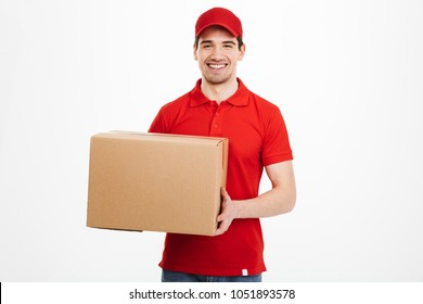 Image of a happy young delivery man in red cap standing with parcel post box isolated over white background.