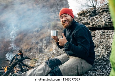 Image of happy young explorer man drinking hot beverage in mountains, sitting near to bonfire, relaxing after trekking. Traveler man in red hat holding a mug of tea after hiking. Travel, people