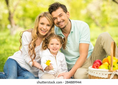 Image of happy young family having picnic outdoors.