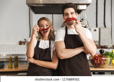Image of happy young friends loving couple chefs on the kitchen having fun with pepper as a moustache.