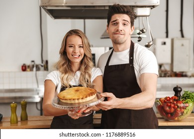 Image of happy young friends loving couple chefs standing on the kitchen holding cake.