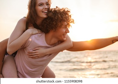 Image of happy young loving couple having fun outdoors on the beach.