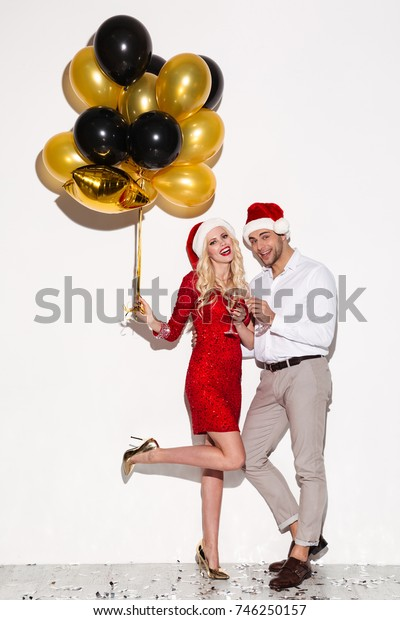 Image of happy young loving couple wearing christmas hats standing isolated over white background wall holding balloons. Looking camera.