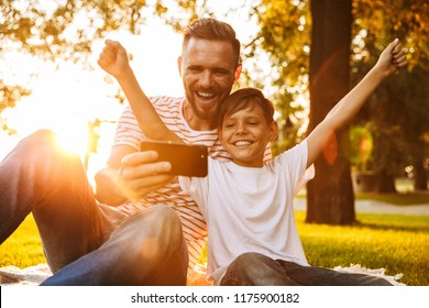 Image of happy young man father have a rest with his son outdoors in park play games with mobile phone.